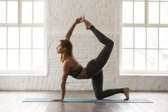 Sporty woman practicing yoga, doing tiger exercise, Bird dog pose. Sporty young woman in grey sportswear, bra and leggings practicing yoga, doing tiger exercise royalty free stock images