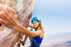 Sporty young woman in helmet rock climbing. High in the mountains Stock Photo