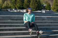 Sporty young woman its on the steps in the park and expressively. Sporty young woman in funny sunglasses sits on the steps in the park and expressively laughing Stock Photos