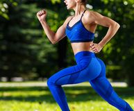 Sporty young woman jogging outdoors in the summer. stock photos