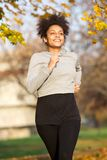 Sporty young woman jogging in the park. Portrait of a sporty young woman jogging in the park Royalty Free Stock Photography