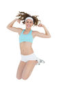 Sporty young woman jumping showing her arm muscles Royalty Free Stock Image