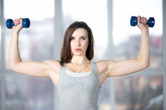 Sporty young woman lifting dumbbells Royalty Free Stock Images
