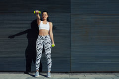 Sporty young woman lifting weights standing with arms tense against black wall outdoors Royalty Free Stock Photos