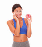Sporty young woman looking at tempting food Stock Image