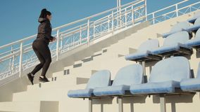 Sporty young woman makes cardio training running up on stairs slow motion