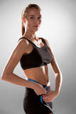 Sporty young woman with measuring tape Stock Photo