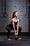 Sporty young woman with muscular body doing crossfit workout with kettlebell against brick wall. Sporty woman in the black sportwear, t-shirt, leggings and Royalty Free Stock Image