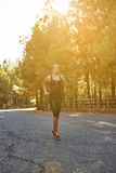 Sporty young woman out jogging alone Stock Photos