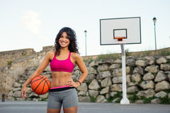 Sporty young woman playing basket outside Stock Photo