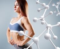 Sporty young woman posing near molecules structure. stock photo