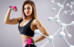 Sporty young woman posing near molecules structure. stock photos