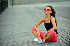 Sporty young woman resting on the beach Royalty Free Stock Images