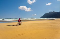 Sporty Young Woman Ride Bicycle On Sand Beach Stock Images