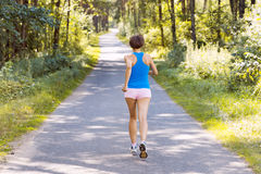 Sporty young woman runner running on the road. In forest Royalty Free Stock Photography
