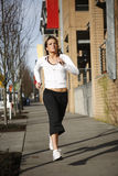 Sporty young woman running. A sporty and attractive woman running in the city Stock Photos