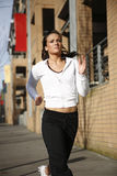 Sporty young woman running. A sporty and attractive woman running in the city Stock Photography