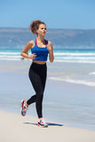 Sporty young woman running on beach. Full length portrait of an sporty young woman running on beach Stock Photo