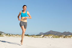 Sporty young woman running on the beach. Full length portrait of sporty young woman running on the beach Stock Photography