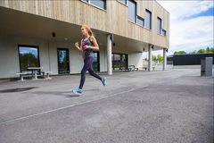 Sporty Young Woman Running By Building. Full length side view of sporty young woman running by building Royalty Free Stock Images