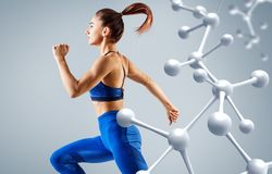 Sporty young woman running and jumping near molecules structure. stock photos