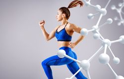 Sporty young woman running and jumping near molecules structure. royalty free stock image