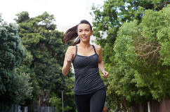 Sporty young woman running outdoors. Portrait of a sporty young woman running outdoors Stock Image