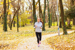 Sporty young woman running in the park. And listening to music. Sport lifestyle. Motion blur Stock Photos