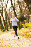 Sporty young woman running in the park. And listening to music. Sport lifestyle. Motion blur Stock Image