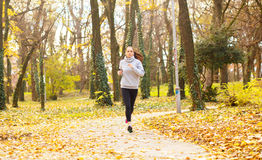 Sporty young woman running in the park. And listening to music. Sport lifestyle. Motion blur Royalty Free Stock Photo