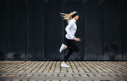 Sporty young woman running on sidewalk in morning Stock Images