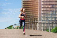 Sporty young woman running and sprinting outside. Portrait of sporty young woman running and sprinting outside at racetrack Stock Image