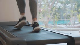 Sporty young woman running on treadmill, close-up feet rear view. Sporty young woman running on treadmill. Close-up of feet, rear view stock footage