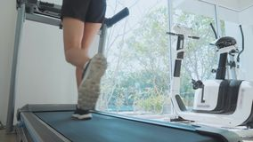 Sporty young woman running on treadmill, close-up rear view. Sporty young woman running on treadmill. Close-up of feet and butt, rear view stock footage
