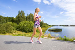 Sporty young woman runs on road along the water Royalty Free Stock Photography