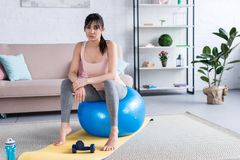 Sporty young woman sitting on fit ball after workout. At home stock images