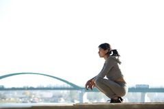 Sporty young woman sitting outdoors Stock Images