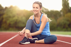 Sporty young woman sitting on a race track. At a sports stadium smiling as she ties her laces on her running shoes backlit by the glow of the morning sun Royalty Free Stock Images
