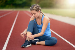 Sporty young woman sitting on a race track. At a sports stadium smiling as she ties her laces on her running shoes backlit by the glow of the morning sun Stock Photos