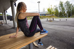 Sporty Young Woman Sitting On Wooden Bench At Park Stock Photo