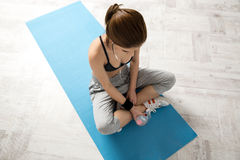 Sporty young woman sitting on the yoga mat. At gym Stock Photo