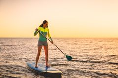 Attractive young woman at stand up paddle board with sunset colors. Sporty young woman at stand up paddle board with bright sunset stock images