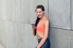 Sporty young woman standing checking her messages Stock Photography