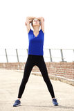 Sporty young woman stretching arms above head Royalty Free Stock Photos