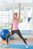 Sporty young woman stretching hand in fitness studio Royalty Free Stock Photo