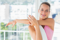 Sporty young woman stretching hands at yoga class Royalty Free Stock Images