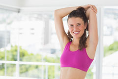 Sporty young woman stretching hands at yoga class Stock Photography