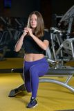 Sporty young woman stretching in leg lunge position on bench in gym Royalty Free Stock Photo