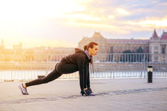 A sporty young woman stretching in the sunset Royalty Free Stock Photo