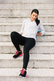 Sporty young woman texting on smartphone Stock Photos